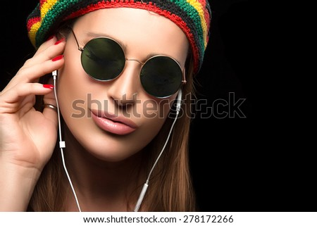 Feeling the Music. Close up Fashionable Young Woman, Wearing Rastafarian Hat and Trendy Round Sunglasses, Enjoying Party Music Through Headphone. Portrait Isolated on Black with Copy Space for Text. - stock photo