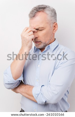 Feeling tired and stressed. Frustrated senior man in shirt touching head with fingers and keeping eyes closed while standing against white background - stock photo