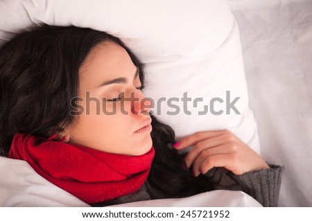Feeling unwell. Closeup image of young sick woman sleeping in bed with sore throat in scarf - stock photo
