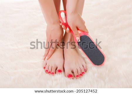 Feet and hands of the girl with the nail file for a pedicure