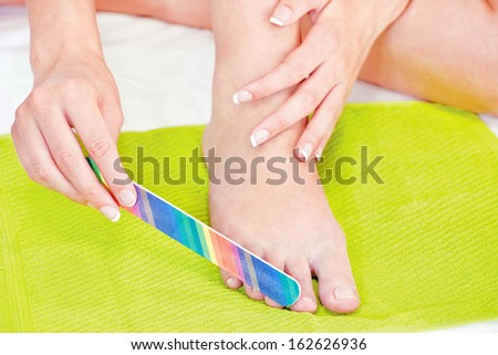 feet beauty treatment with nail file