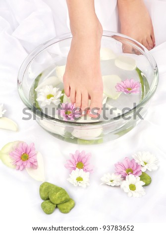 Feet dipped in aromatherapy bowl - stock photo
