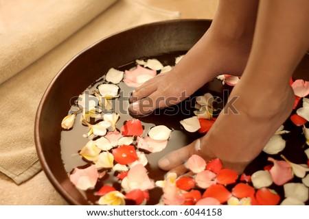 Feet dipped into spa & aromatherapy bowl - stock photo