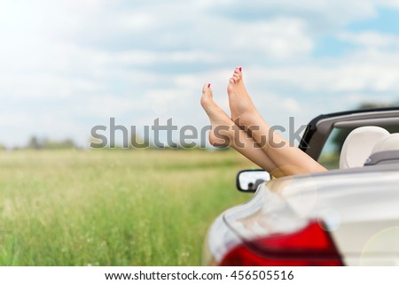 Feet hanging out of convertible