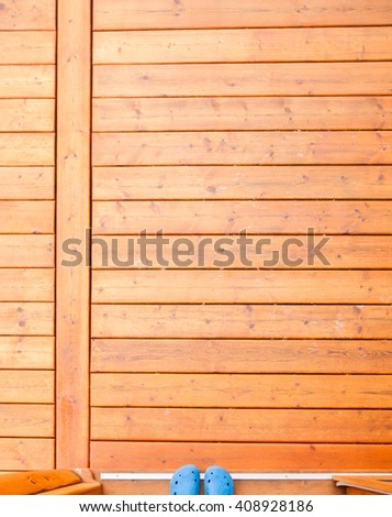 Feet in blue rubber shoes in open doorway onto wooden porch or deck from straight above with rich warm wood grain textures and colors