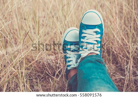 Feet in blue sneakers and wear jeans on the grass. with colored vintage style