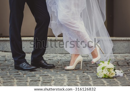 Feet in footwear of the groom and the bride  - stock photo