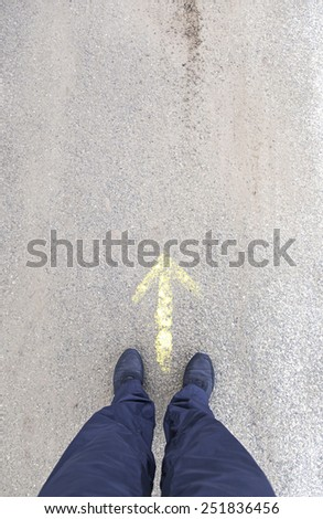 Feet in front of an arrow, detail of a direction arrow, sign - stock photo
