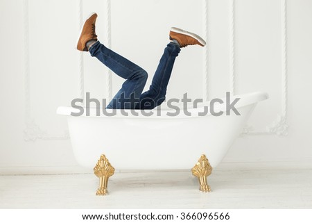 Feet in jeans and gym shoes looking out of a white bath in a white interior. White interior. Feet in jeans and gym shoes. - stock photo