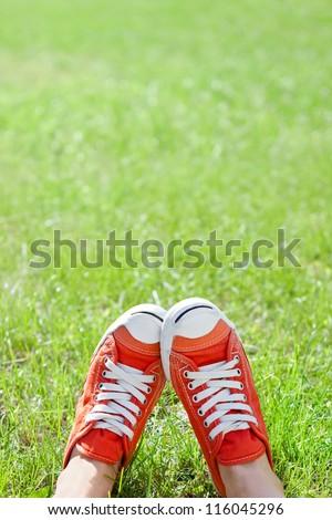 Feet in sneakers in green grass - stock photo