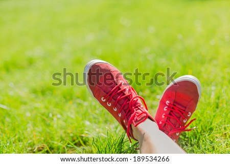 Feet in sneakers in green grass. Summer time  - stock photo
