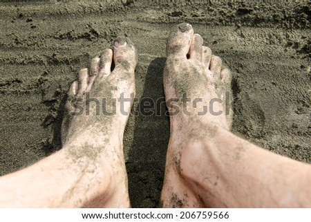 Feet in the sand, the concept of shipwreck and bankrupt