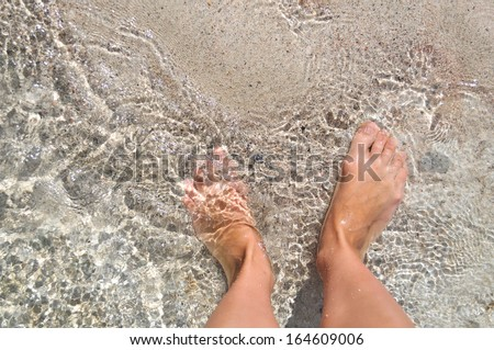 Feet in the water on the sand. Mediterranean sea, the island of Crete. Greece. - stock photo