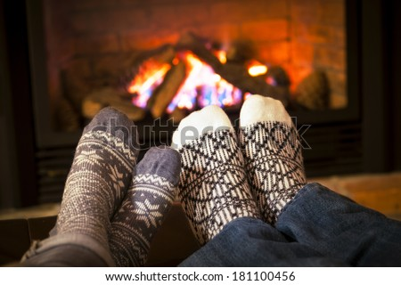 Feet in wool socks warming by cozy fire - stock photo