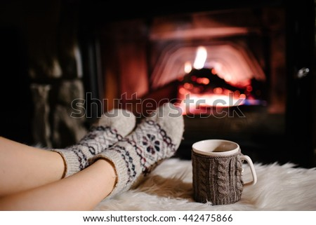 Feet in woollen socks by the Christmas fireplace. Woman relaxes by warm fire with a cup of hot drink and warming up her feet in woollen socks. Close up on feet. Winter and Christmas holidays concept - stock photo