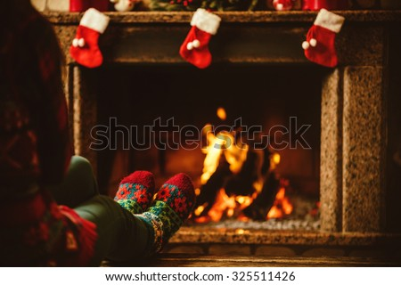 Feet in woollen socks by the fireplace. Woman relaxes by warm fire and warming up her feet in woollen socks. Close up on feet. Winter and Christmas holidays concept. - stock photo