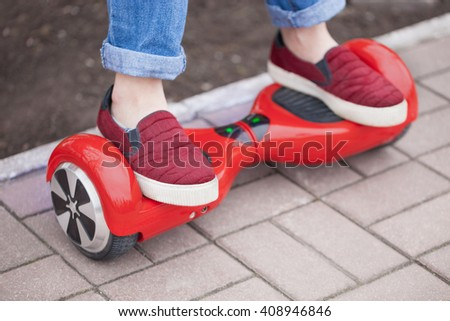 Feet of a girl in marsala shoes riding on modern red electric mini segway or hover board scooter. Trending new transport, fun and easy to ride,produces no air pollution to the atmosphere.  - stock photo