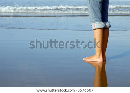 Feet of a girl watching the ocean - stock photo