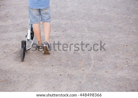 Feet of a kid boy with scooter on a sunny day.  child outdoors, active sport kids