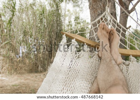 Feet of a person relaxing in a hammock