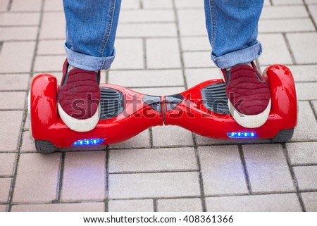 Feet of a woman riding on modern red electric mini segway or hover board scooter. New transportation technology is so fun and easy to ride,produces no air pollution to the atmosphere. - stock photo