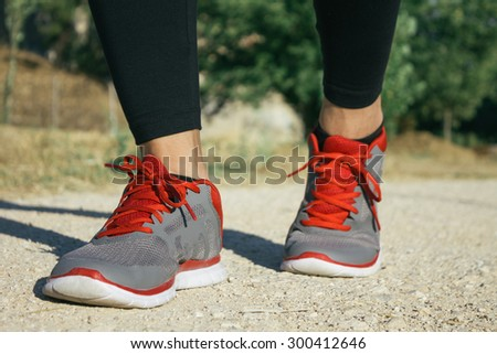 Feet of a woman runner in a sand track