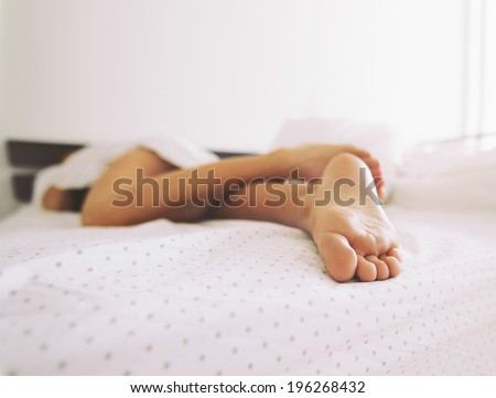 Feet of a woman sleeping in bed at home. Legs of a female lying on bed - Indoors - stock photo