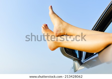 Feet of a young girl from the window of a car - stock photo