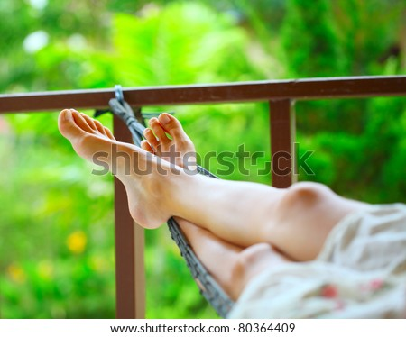 Feet of a young woman lying in hammock in a garden