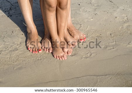 feet of child and mom in the sea sand, from above - stock photo