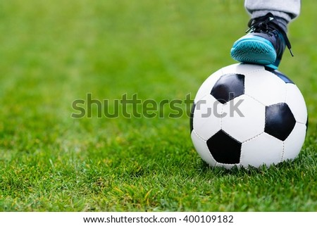 Feet of child on football / soccer ball on grass. Child playing football. Copyspace - stock photo