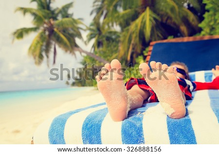 feet of child relaxed and enjoying summer beach vacation
