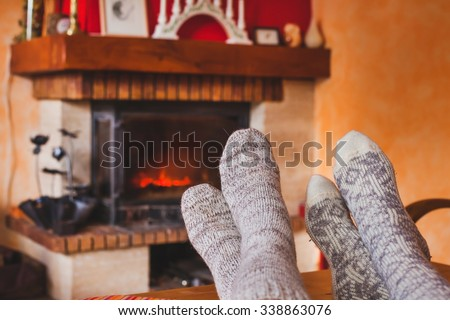 feet of couple near cozy fireplace in winter, family at home near fire - stock photo