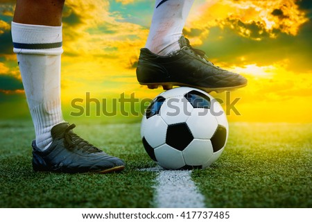 feet of football player tread on soccer ball for kick-off