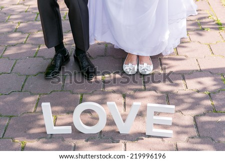 Feet of groom and bride and white love letters - stock photo