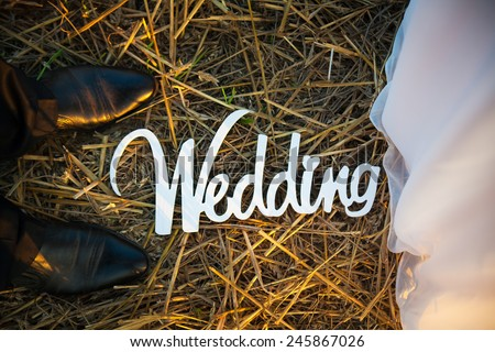 Feet of groom and bride and white wedding letters in straw - stock photo