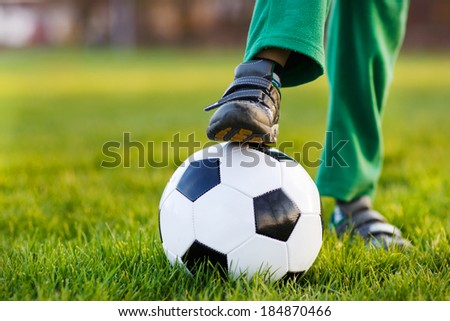 Feet of little boy with football on football field, outdoors.