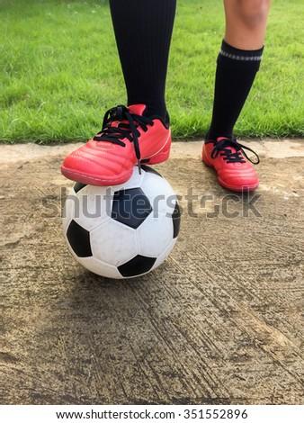 Feet of little boy with football on football field, outdoors. - stock photo