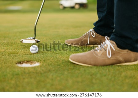 Feet of male golf player putting at green.  - stock photo
