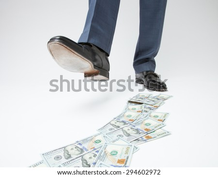 Feet of man in black shoes going by money track - closeup shot - stock photo