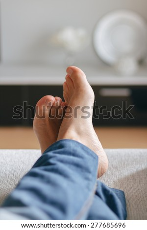 Feet of man relaxing on the sofa - stock photo