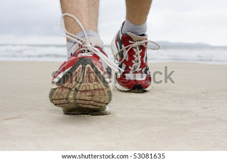 Feet of man with sneakers jogging on a beach - stock photo