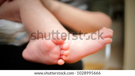 Feet of newborn baby in the hand of mother