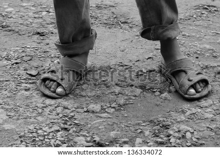 feet of poor boy covered with mud - stock photo
