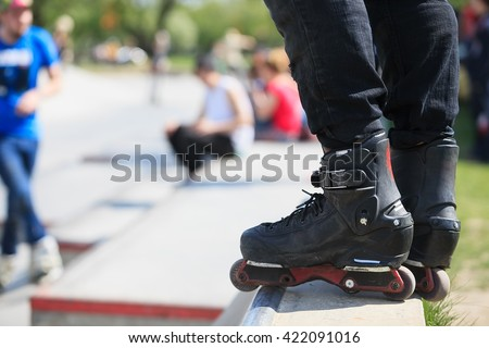 Feet of rollerblader wearing aggressive inline skates standing on top of concrete ramp in outdoor skate park. Extreme sports athlete wearing roller blades for tricks and grinds - stock photo