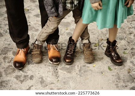 feet of three people in the autumn shoes, father, son, daughter - stock photo