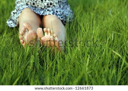 feet of woman resting in green grass - stock photo