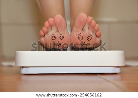 Feet on bathroom scale with hand drawn cute faces - stock photo