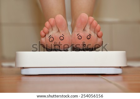 Feet on bathroom scale with hand drawn sad cute faces - stock photo