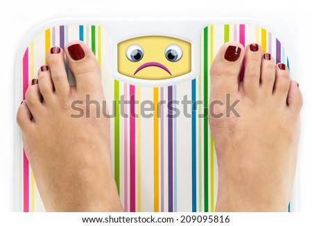 Feet on bathroom scale with sad cute face on dial - stock photo
